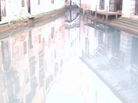 In the afternoon the still canal waters reflect Venetian images.